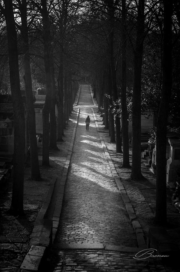Uma caminhante solitária no cemitério (Cimitière du Père Lachaise, Paris, France).